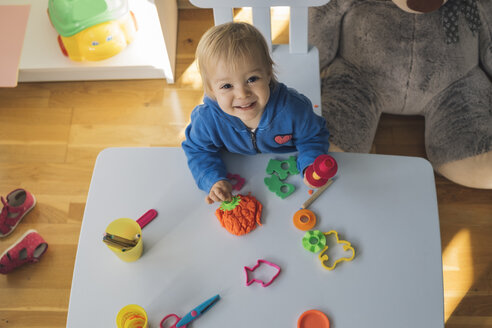 Portrait of smiling baby girl playing with modeling clay in children's room - MOMF00554