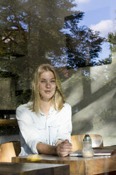 Portrait of blond woman in a cafe looking out of window - LMJF00014