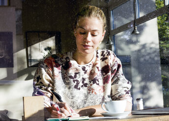 Portrait of woman in a cafe writing on notebook - LMJF00020