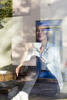 Woman sitting in a cafe drinking cup of coffee while looking out of window - LMJF00023
