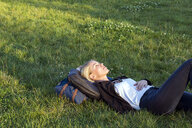Woman lying on a meadow in a park relaxing - LMJF00029