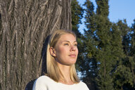 Portrait of daydreaming blond woman leaning at tree trunk looking at distance - LMJF00032