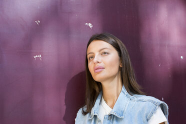 Portrait of daydreaming young woman in front of purple background - LMJF00035