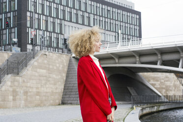 Germany, Berlin, blond young woman with ringlets wearing red coat - LMJF00056