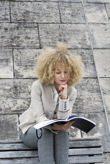 Portrait of blond woman with ringlets sitting on bench looking at booklet - LMJF00059
