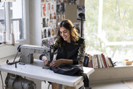 Smiling young fashion designer using sewing machine in her atelier - AFVF02054