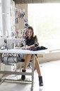 Young designer using sewing machine in an atelier - AFVF02057