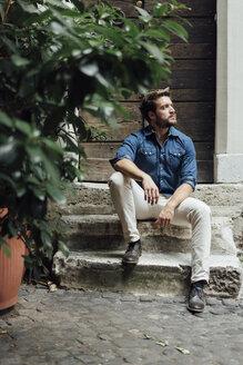 Businessman sitting on steps in a courtyard - BOYF01087