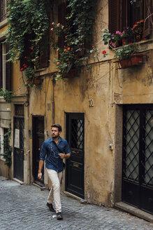 Businessman using smartphone and earphones on the street - BOYF01111