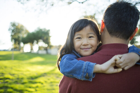 Portrait of cute girl smiling while carried by father in park - TGBF01743