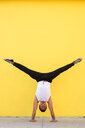 A man doing a handstand against a yellow background - INGF08096
