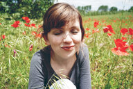Portrait of a smiling woman on a grassy field - INGF08111