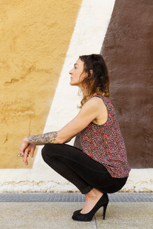 Side view of a young woman crouching against a patterned wall in Spain - INGF08126
