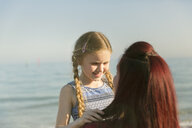 Affectionate mother holding daughter on sunny ocean beach - CAIF22256