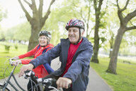 Active senior couple riding bikes in park - CAIF22274