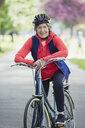 Portrait smiling, confident active senior woman riding bike in park - CAIF22277