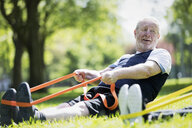 Active senior man exercising in park, stretching with resistance band - CAIF22283