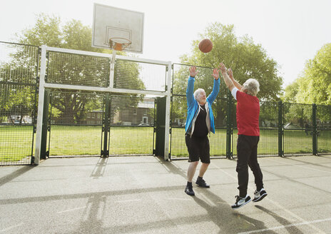 Active senior men friends playing basketball in sunny park - CAIF22286