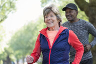 Smiling active senior woman power walking in park - CAIF22301