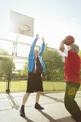 Active senior men playing basketball in sunny park - CAIF22331