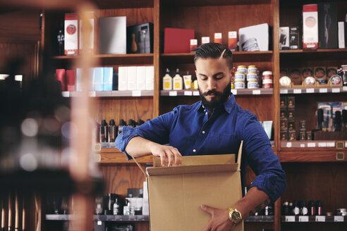 Salesman unpacking cardboard box while standing against rack in deli - MASF09782