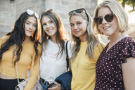 Portrait of smiling friends standing in city during summer - MASF09812