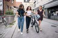 Full length of friends talking while walking with bicycle on street in city - MASF09839