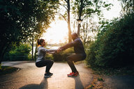 Male and female athletes holding hands while practicing chair position on road in park - MASF09848