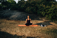 Full length of young woman practicing yoga on field in park - MASF09869