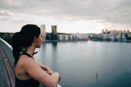 Side view of female athlete looking at city while standing on footbridge over sea - MASF09893