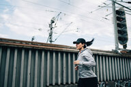 Young sportswoman jogging by fence on footbridge in city - MASF09902