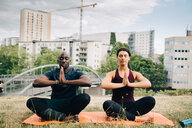 Multi-ethnic friends practicing yoga on field against buildings in city - MASF09905