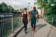 Multi-ethnic male and female athletes talking while walking on footbridge in city - MASF09911