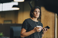 Female executive holding coffee cup while talking with earphones during phone call in office - MASF09947