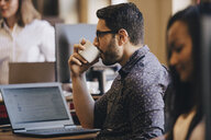 Mid adult businessman drinking coffee with laptop on desk in office - MASF09962