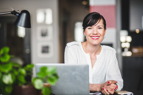 Portrait of confident entrepreneur sitting at desk in office - MASF09968