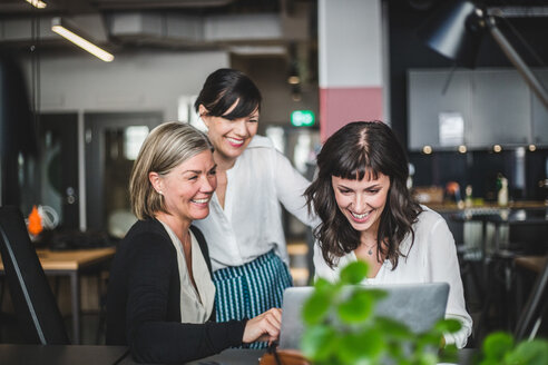 Creative businesswomen smiling while discussing over laptop at desk in office - MASF09971
