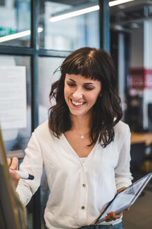 Smiling businesswoman holding digital tablet while writing on whiteboard in office - MASF10028