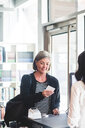 Businesswoman reading card while standing at counter in office - MASF10061