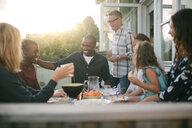 Cheerful multi-generation family enjoying lunch at porch - MASF10076