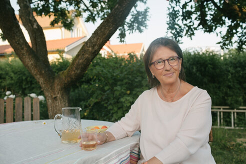Portrait of smiling woman holding drink while sitting at table in backyard - MASF10079