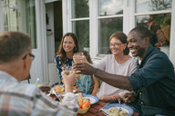 Happy multi-generation family toasting drinks at table during garden party - MASF10091