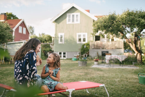 Smiling mother and daughter talking while sitting on lounge chair in backyard - MASF10094