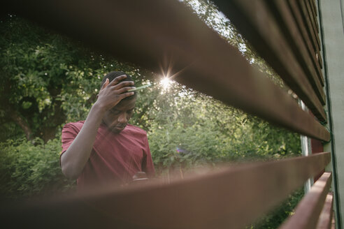 Boy touching head while using mobile phone seen through fence in backyard - MASF10097