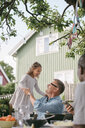 Playful girl standing by grandfather in backyard during garden party - MASF10100