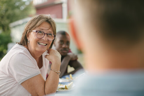 Smiling senior woman looking away while sitting at table during garden party - MASF10109