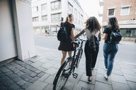 Rear view of friends with bicycle walking on cobbled street in city - MASF10112