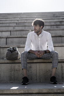 Young man with headphones sitting on stairs outdoors - GIOF04824
