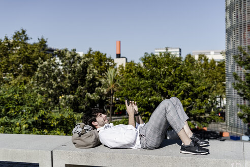 Smiling young man lying on a wall outdoors using cell phone - GIOF04827