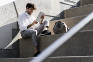 Smiling young man sitting on stairs outdoors using tablet - GIOF04836